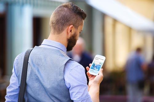 Mann nutzt Smartphone unterwegs