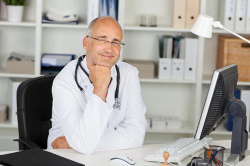 Arzt am Schreibtisch vor PC