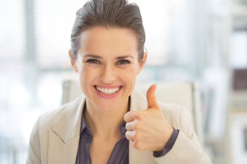 Lächelnde Geschäftsfrau zeigt Daumen hoch